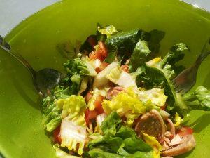 Salat mit Tomate Zwiebeln und Schinkenröllchen